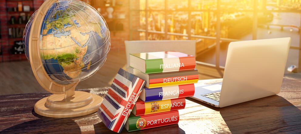 Sprachbücher, Globus und Laptop liegen auf einem Tisch