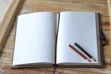 Kreatives Schreiben: Zwei Bleistifte liegen in unbeschriebenem Notizbuch