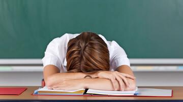 Unterrichtsstörungen: Lehrerin mit Kopf auf dem Pult