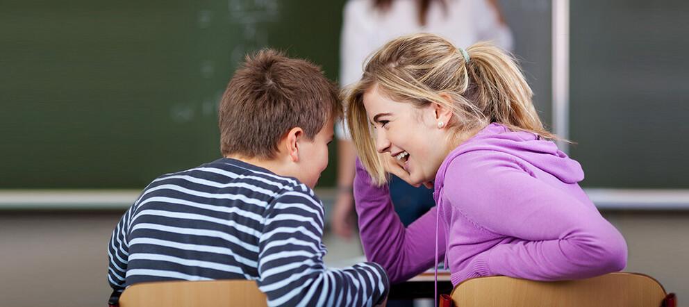 Zwei Schüler unterhalten sich im Unterricht - Symbolhaft für Unterrichtsstörungen