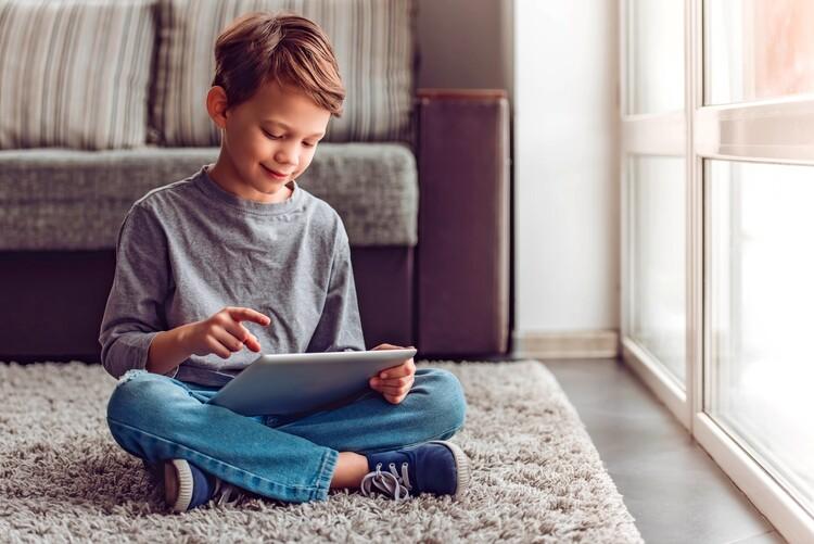 Kind sitzt mit Tablet auf dem Boden