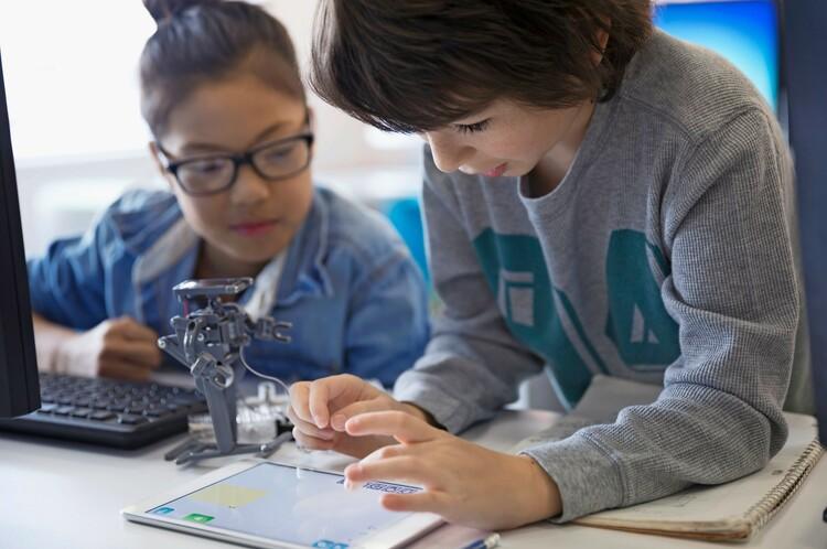 Zwei Schüler experimentieren mit Tablet und Roboter
