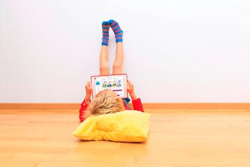 Digitale Didaktik: Kind mit Tablet in entspannter Haltung