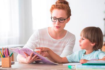 Schulpädagogik: Lehrerinn mit Schüler beim Üben